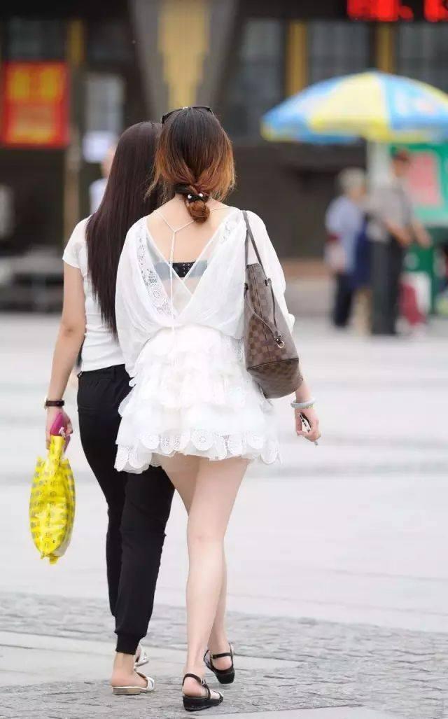 街拍姐姐轻纱有高露背的小美女,小马尾白色短裙踢性感图片