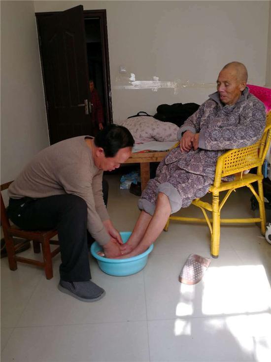 周口一中学校长为九旬父亲洗脚暖心照片走红网络
